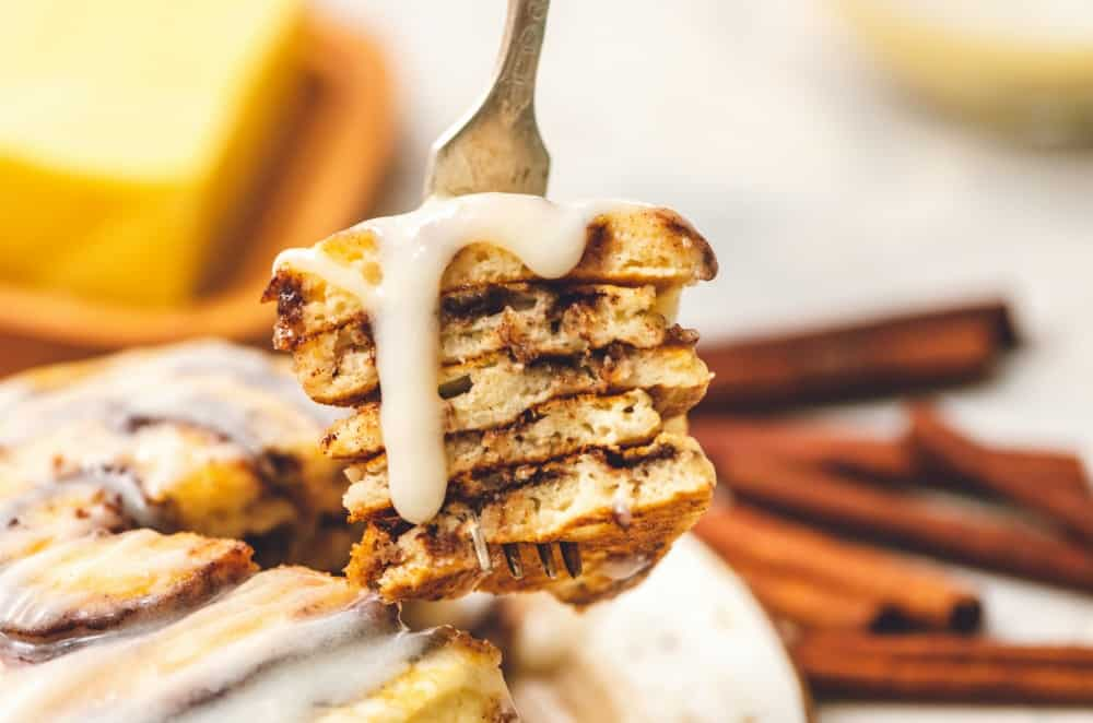 Cinnamon roll pancakes layered on top of each other with the cream cheese glaze.