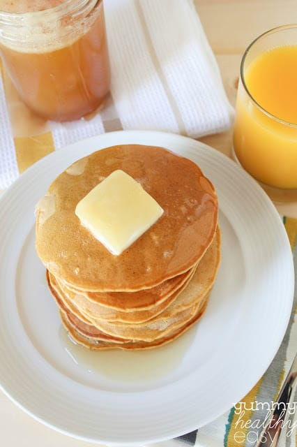 Stack of pumpkin pancakes on a white plate.