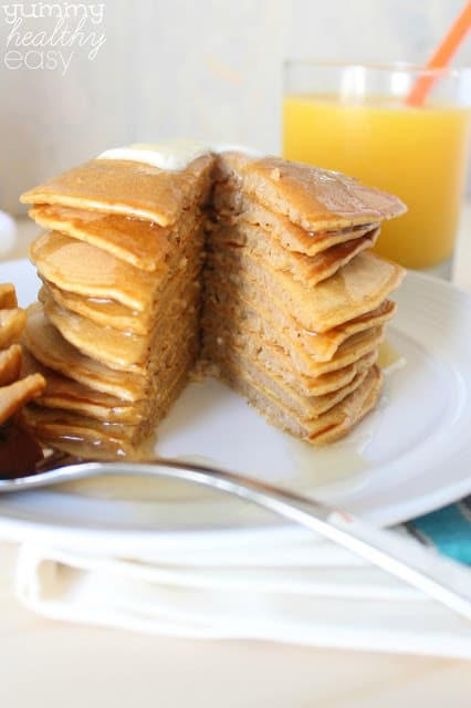 Stack of pumpkin pancakes with a slice cut out.