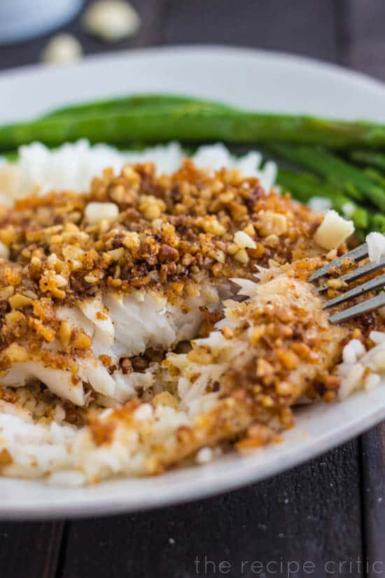 White plate with macadamia crusted talapia and asparagus.