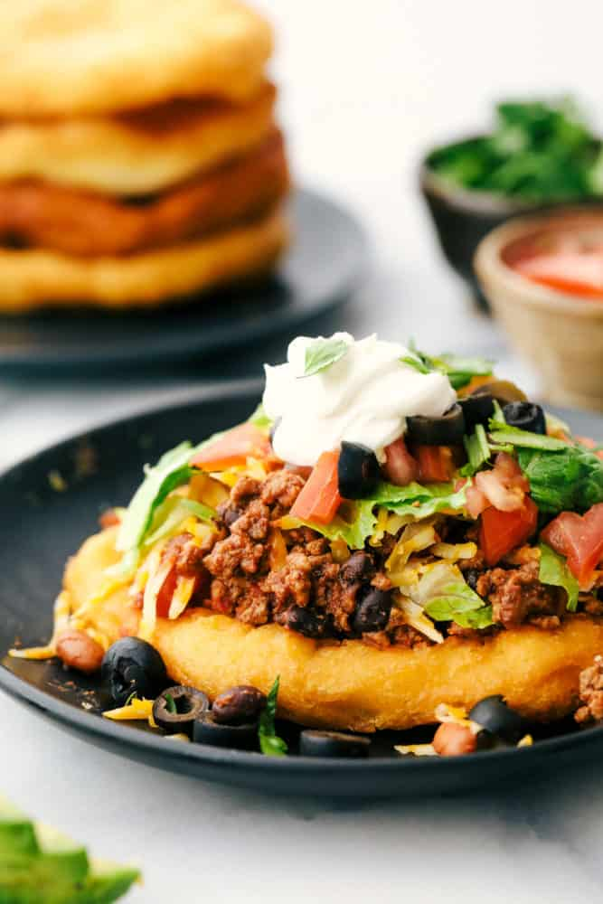 Navajo taco on a plate with beans, ground beef tomatoes, lettuce, cheese and sour cream.