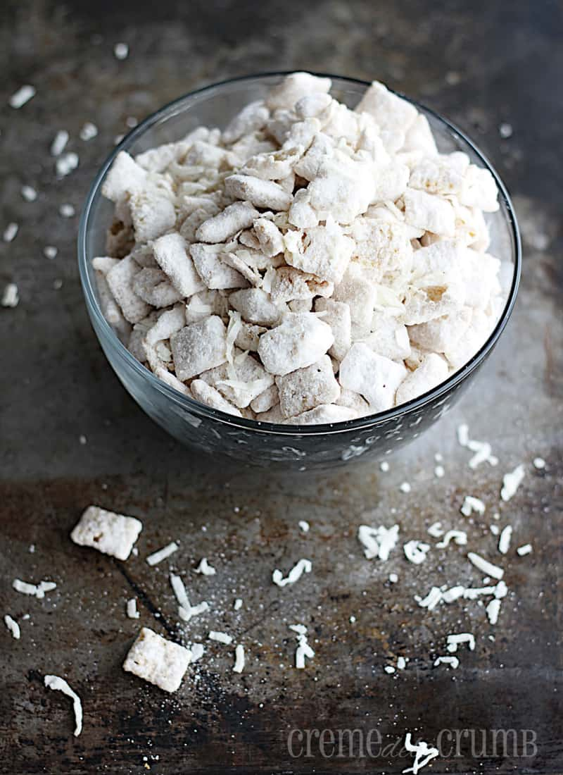 Vanilla coconut muddy buddies in a glass bowl.