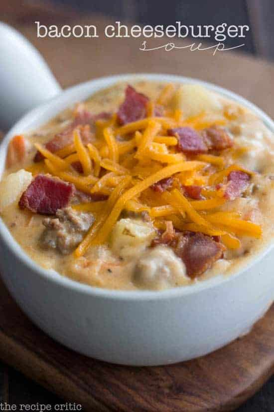 Bacon cheeseburger soup in a white bowl with shredded cheese and bacon crumbles as garnish.