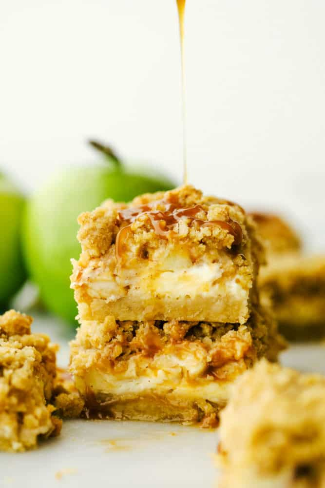 Two caramel apple cheesecake bars stacked on top of each other with caramel being drizzled over top.