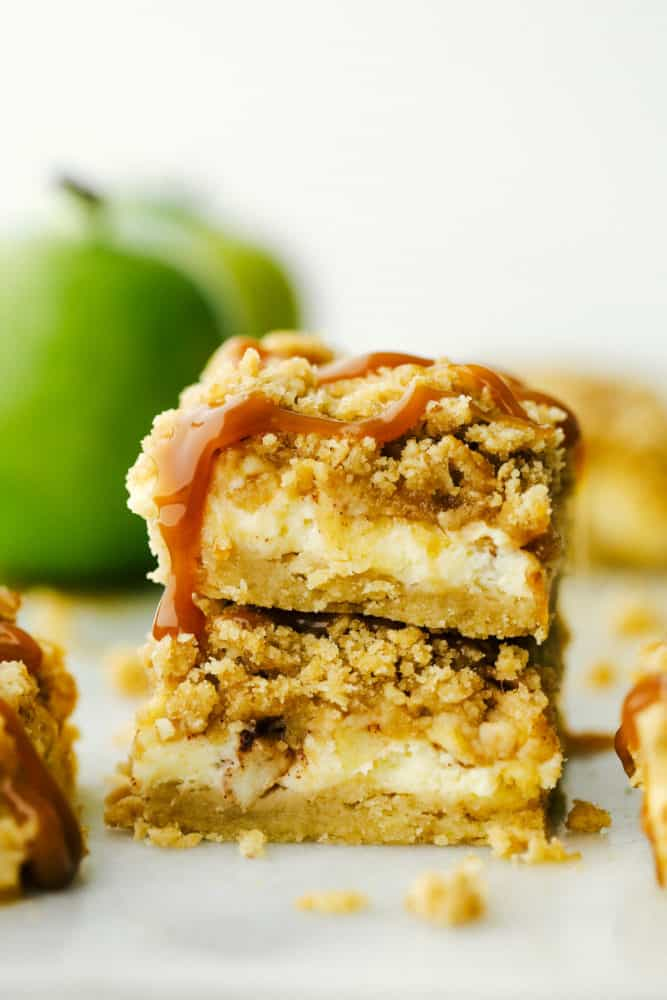 Two caramel apple cheesecake bars stacked on top of each other.