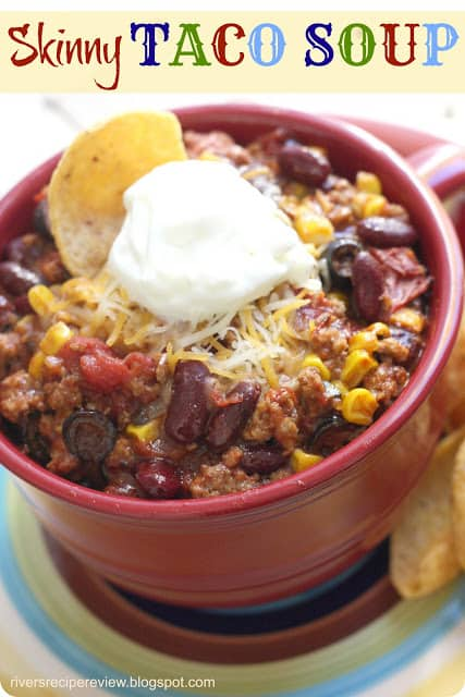 Skinny Taco soup in a red bowl with a dollop of sour cream and tortilla chip.