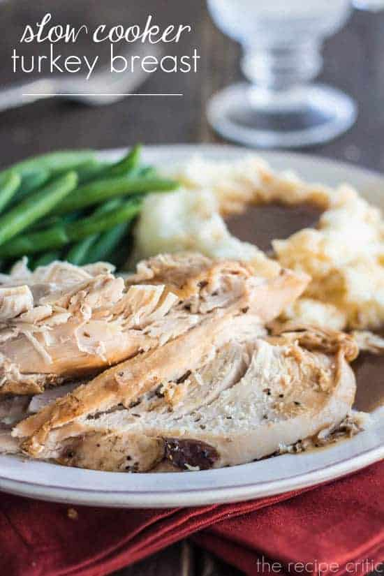 Slow cooker turkey breast pieces on a plate with mashed potatoes and gravy and green beans.