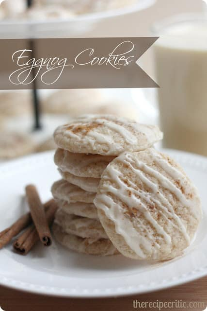 Eggnog cookies stacked on a white plate with cinnamon sticks beside them.