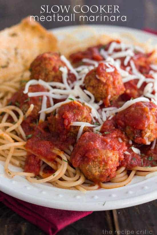 Slow cooker meatball marinara with spaghetti noodles and garlic bread on a white plate.