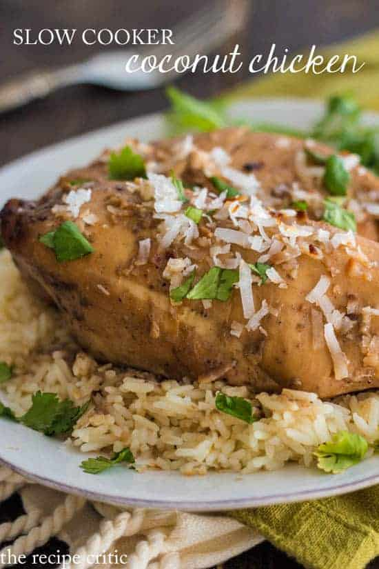 Slow Cooker coconut chicken with coconut garnish, sitting on rice and a white plate.