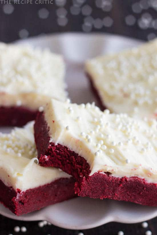 Red Velvet Sugar Cookie Bars on a white plate with a bite taken out of one.