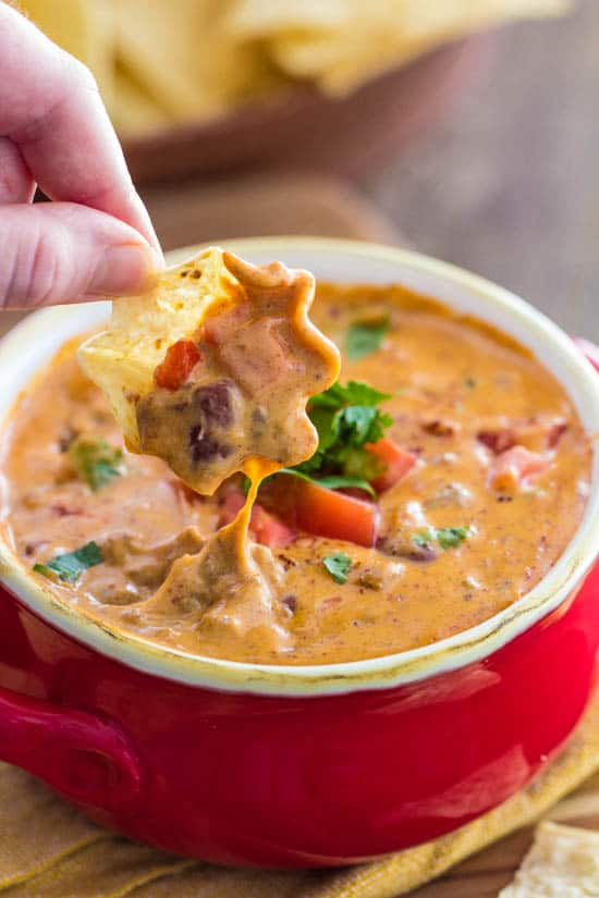 Close up of Chili Queso in a red serving cup with a person dipping a tortilla chip into it.
