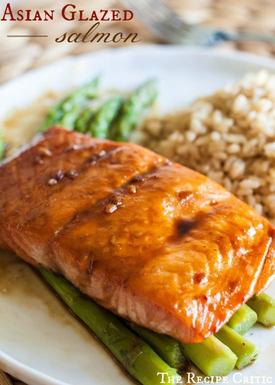 Asian Glazed Salmon over asparagus on a white plate.