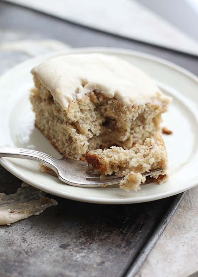 Browned Butter Banana Cake with Brown Sugar Frosting on a white plate with a fork taking a bite out of it.