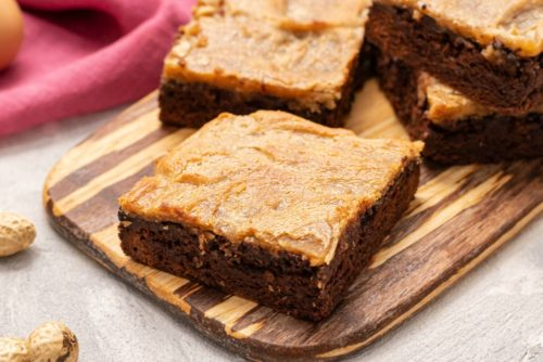 Peanut Butter Cheesecake Brownie Bars on a wooden cutting board.