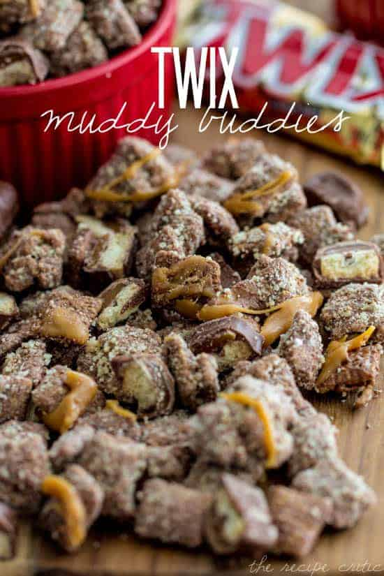 Twix Muddy Buddies on a wooden tables. There are some in a red serving bowl as well.