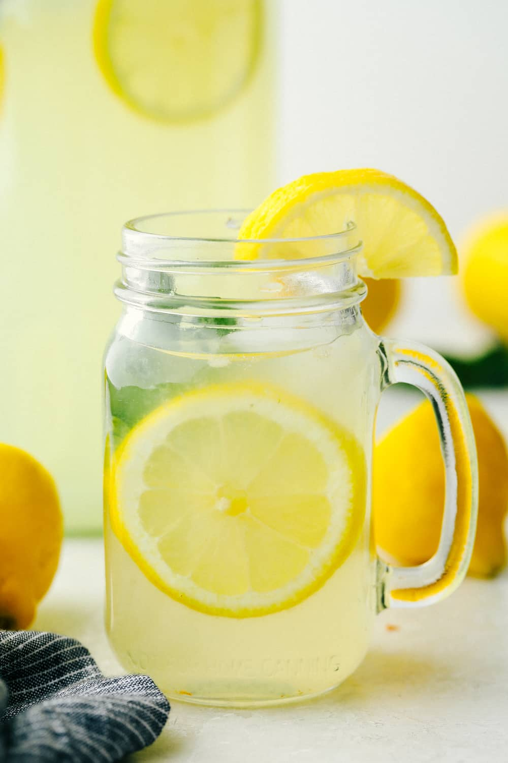 Lemonade ready to drink in a clear mason jar with lemons and mint garnish.