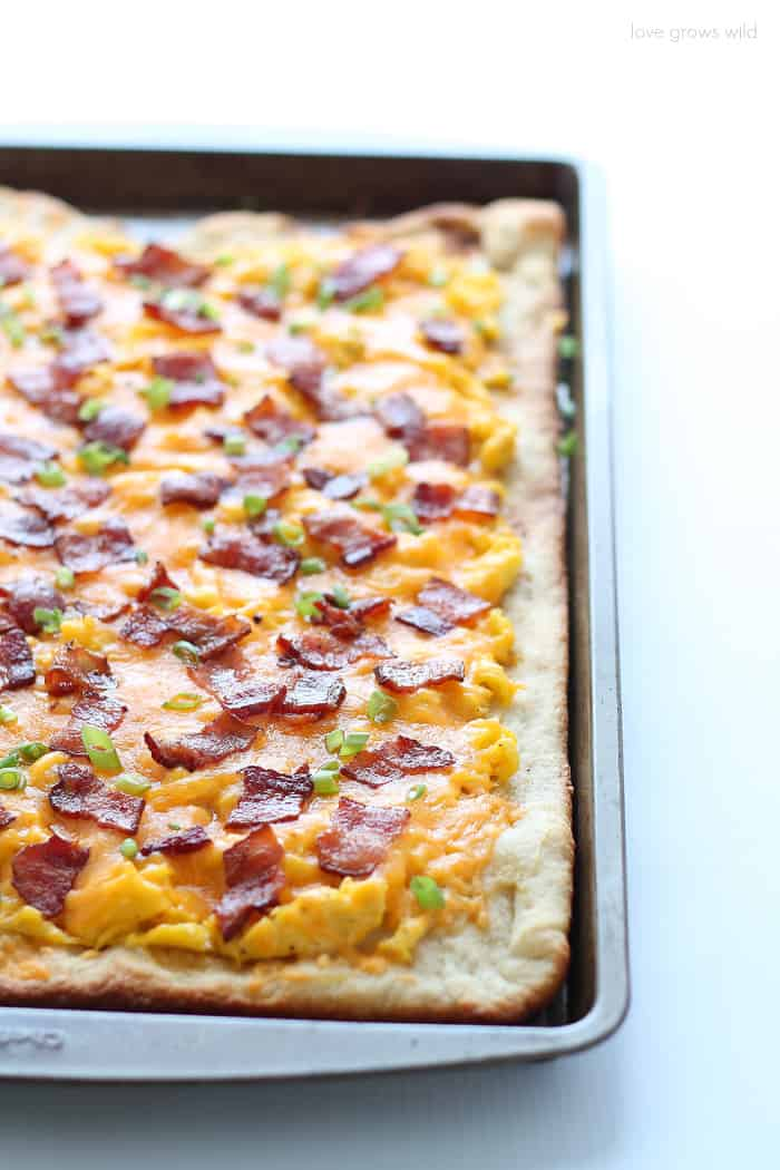 The perfect breakfast pizza topped with soft scrambled eggs, crispy bacon, and lots of melty cheddar cheese!