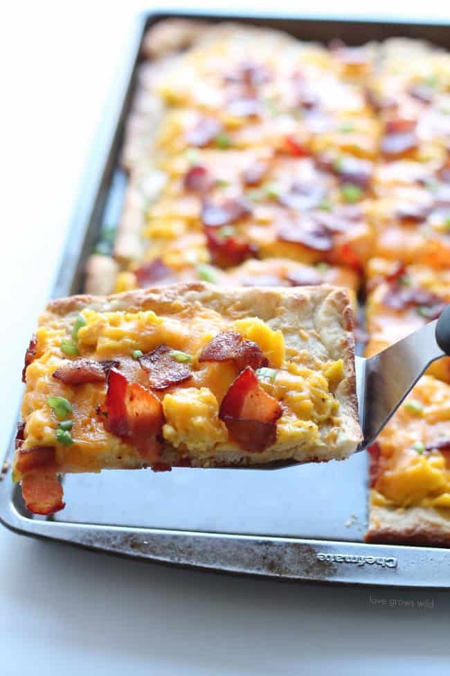 A slice of Bacon and Cheddar Breakfast Pizza being removed from the baking sheet.