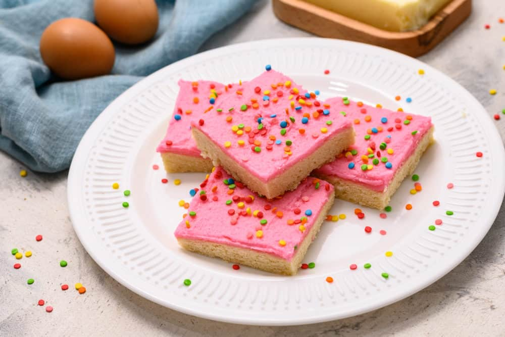 Sugar cookie bars stacked on top of each other with sprinkles on a white plate.