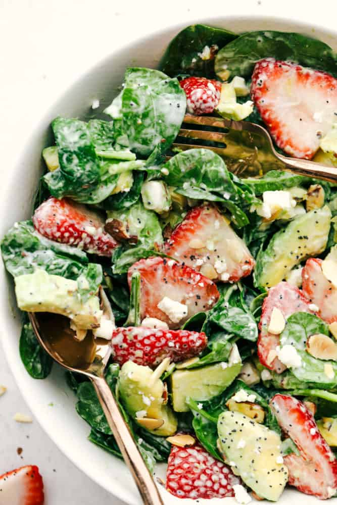 Strawberry avocado spinach salad with poppyseed dressing tossed together and put in a bowl with a fork and spoon.