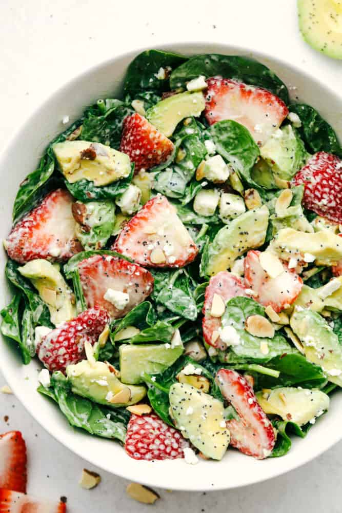 Strawberry, avocado spinach salad with poppyseed dressing mixed together in a white bowl.