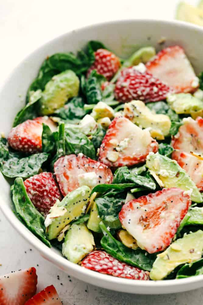 Strawberry avocado spinach salad tossed together in a white bowl and ready to serve.