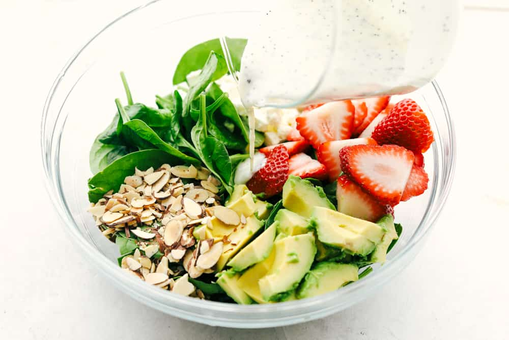 Ingredients to make strawberry avocado spinach salad in a glass bowl with poppyseed dressing being poured over top.