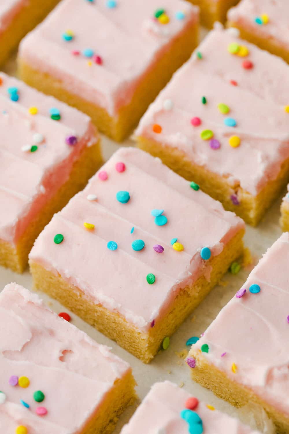 Sugar cookie bars cut into squares with sprinkles on top.