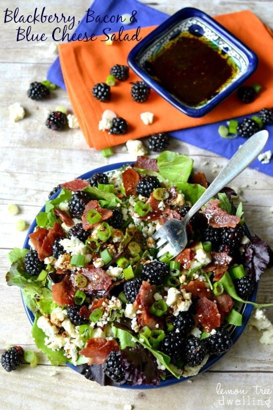 Blackberry, Bacon & Blue Cheese Salad in a blue bowl with a metal fork and dressing on the side.