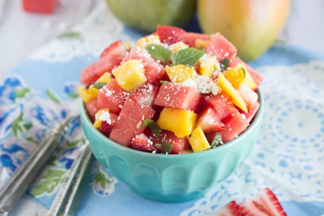 Fresh watermelon and Feta Salad in a blue bowl with metal forks.