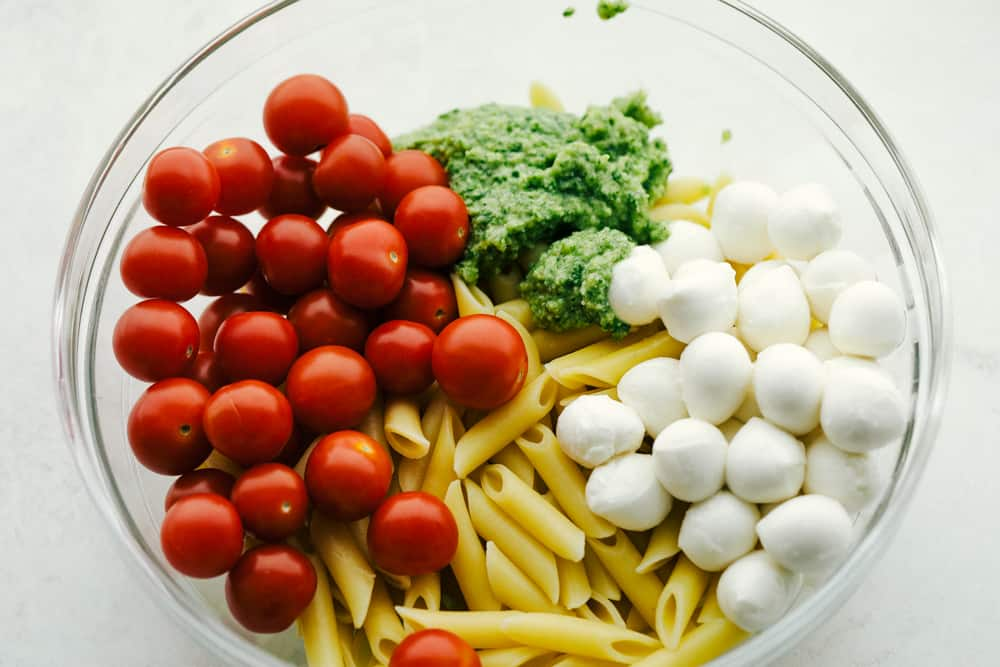 Ingredients for Caprese Pasta Salad in a white bowl.