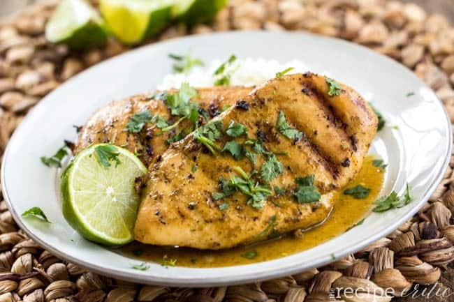 Grilled Lime Coconut Chicken on a white plate with sliced lime on the side.