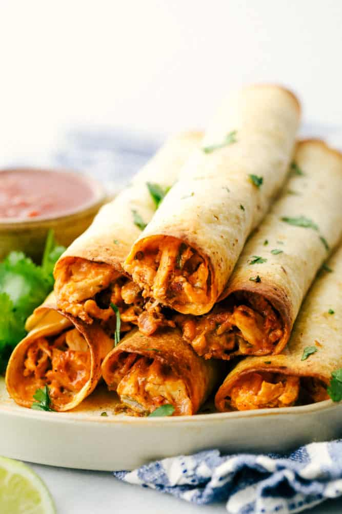 Chicken taquitos stacked on top of each other on a plate.
