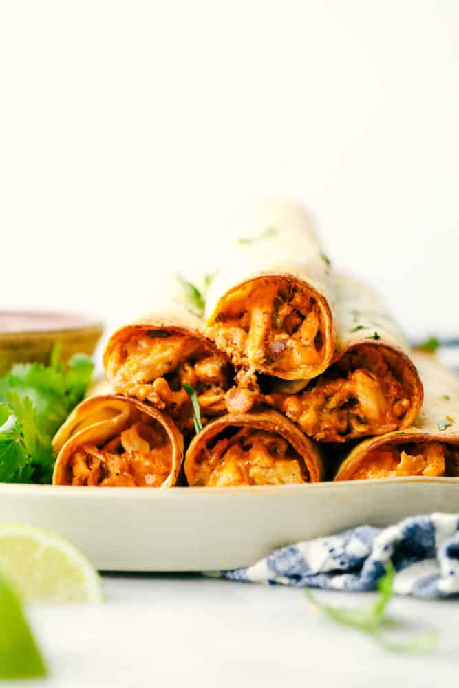 Cream cheese chicken taquitos are stacked on top of each other with lime wedges as a garnish.
