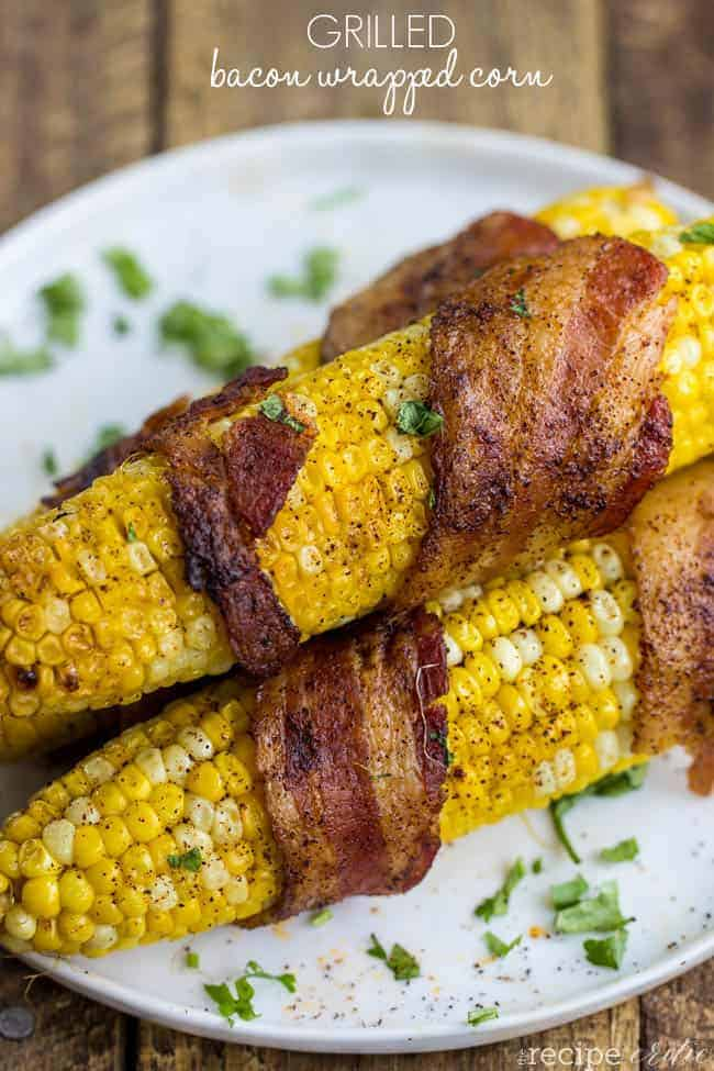 Grilled bacon wrapped corn on the cob laying on a white plate.