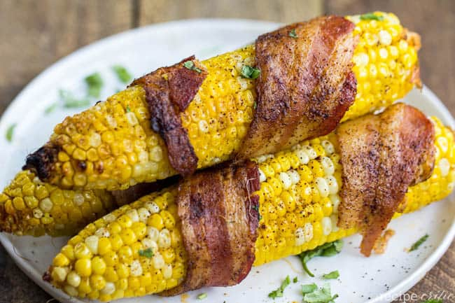 Grilled bacon corn on the cob laying on a white plate.