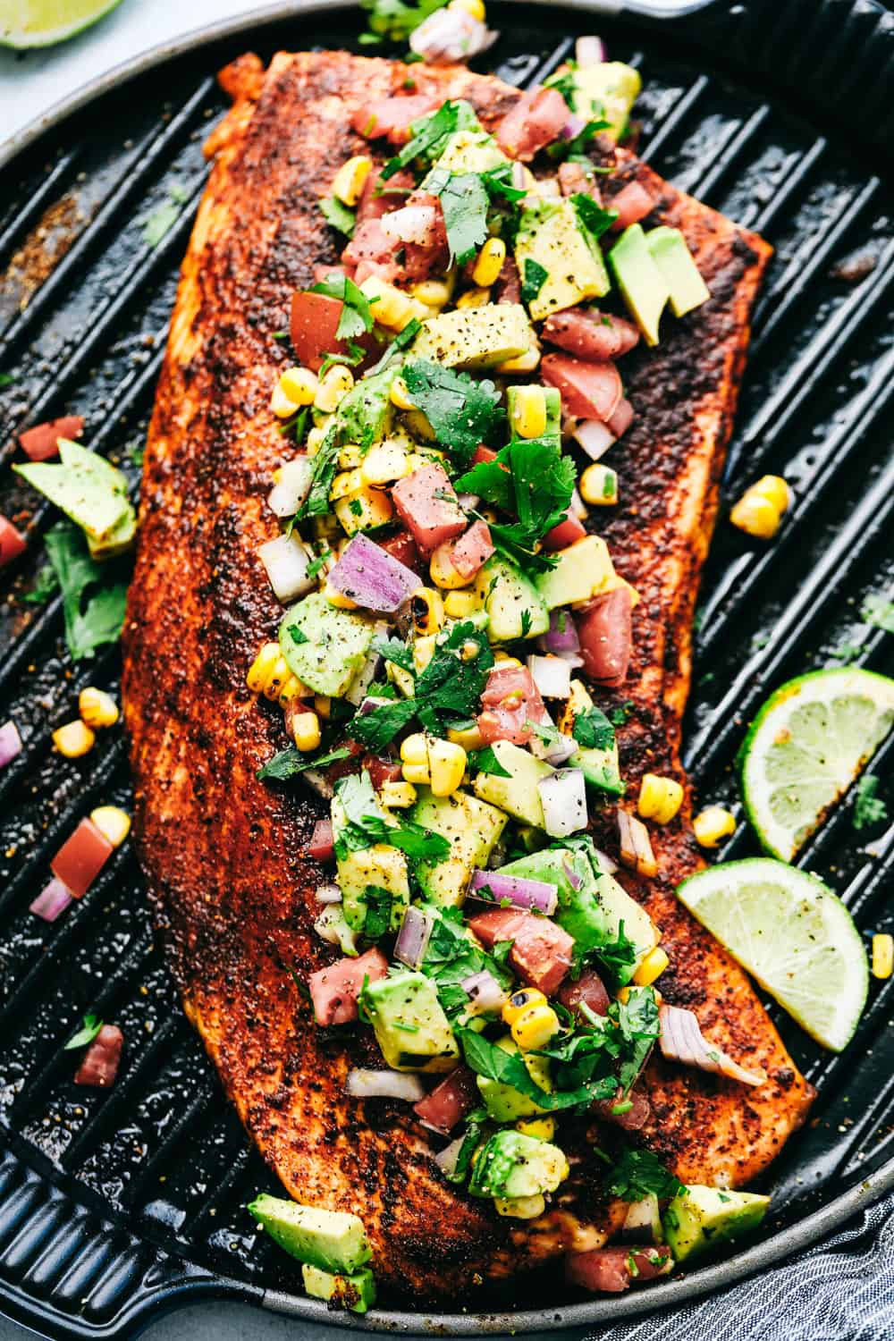 Grilled Salmon topped with Avocado Salsa on a grill.