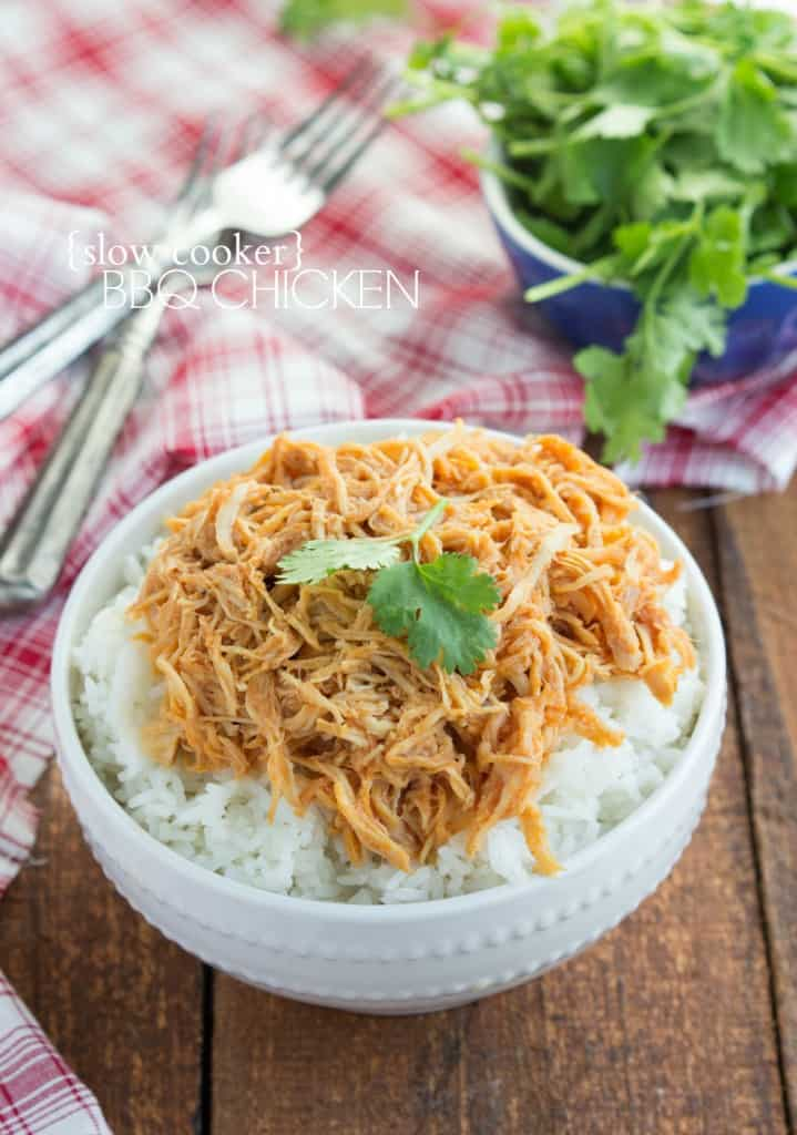 Slow cooker bbq chicken in a white bowl over top of  rice.