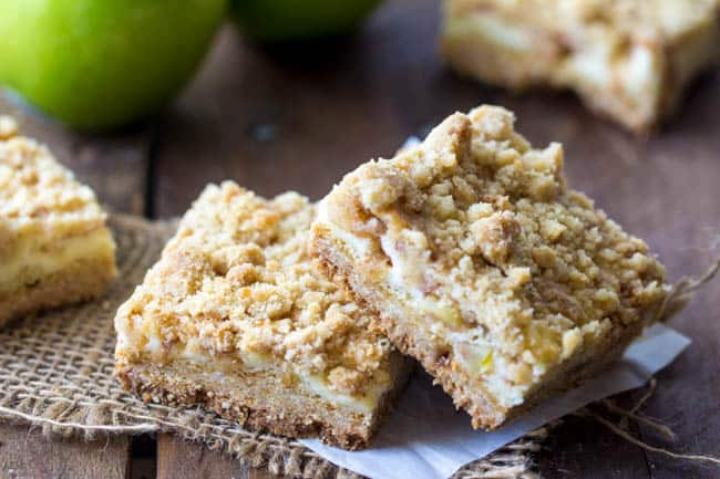 sour cream apple crumb bars stacked on top of each other.