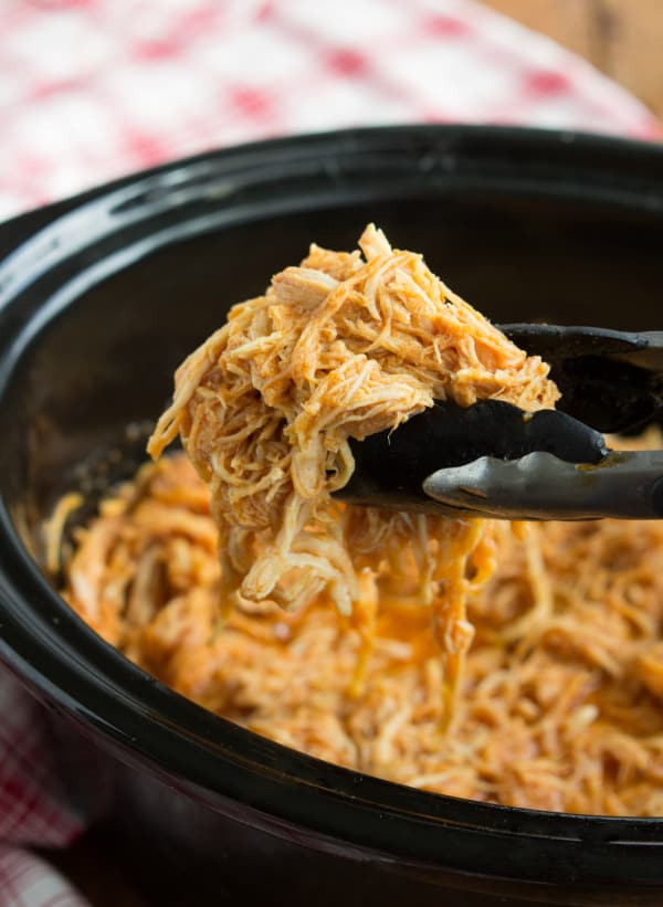 BBQ chicken in a slow cooker with tongs serving it.