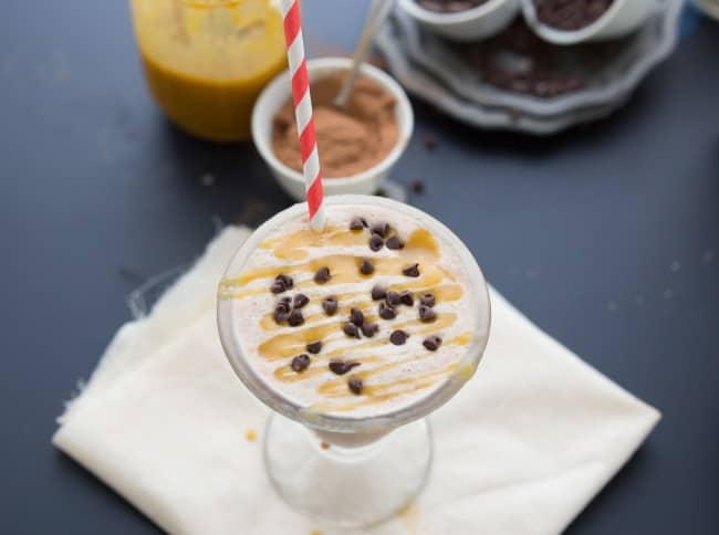 Overhead shot of milkshake with a straw in the drink glass and caramel with chocolate chips on top.