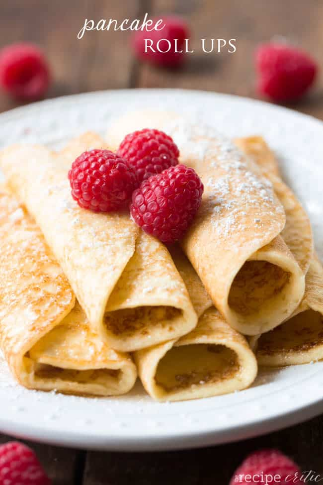 Pancake roll ups stacked on top of each other with three raspberries on top and sprinkled with powdered sugar.