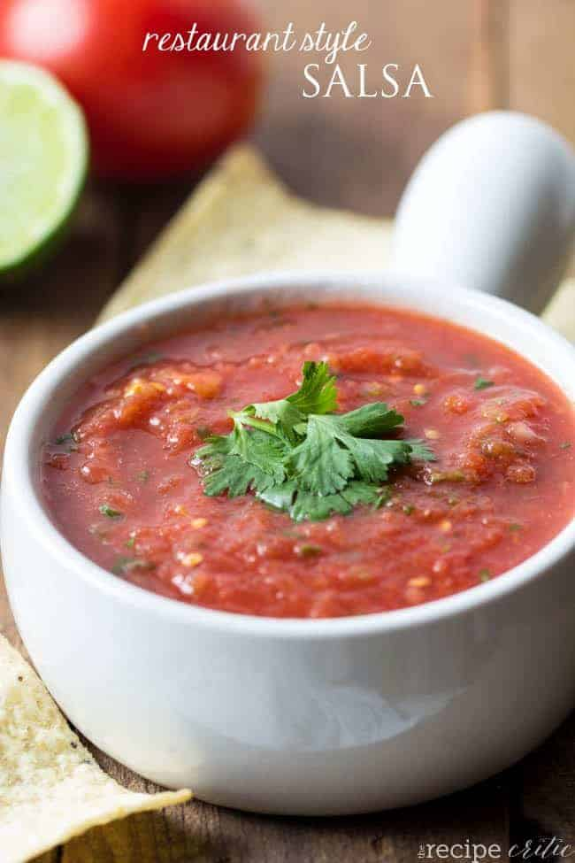 Restaurant style salsa in a white bowl with chips all around.