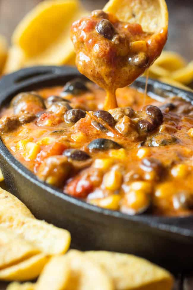 Beefy enchilada dip in a black bowl with a chip being dipped in the dip.