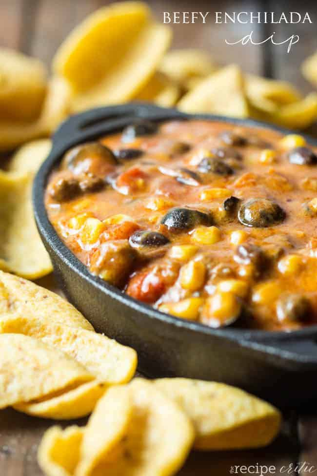 Beefy enchilada dip in a black bowl with frito lay chips around the side.