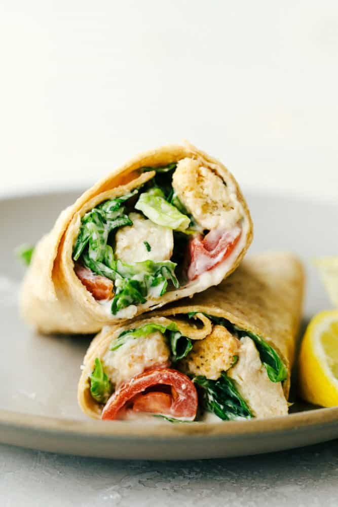 Two parts of a wrap stacked on each other on a plate.