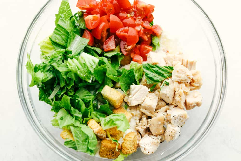 Fresh Ingredients for the Chicken Caesar Salad Wrap in a clear glass bowl.