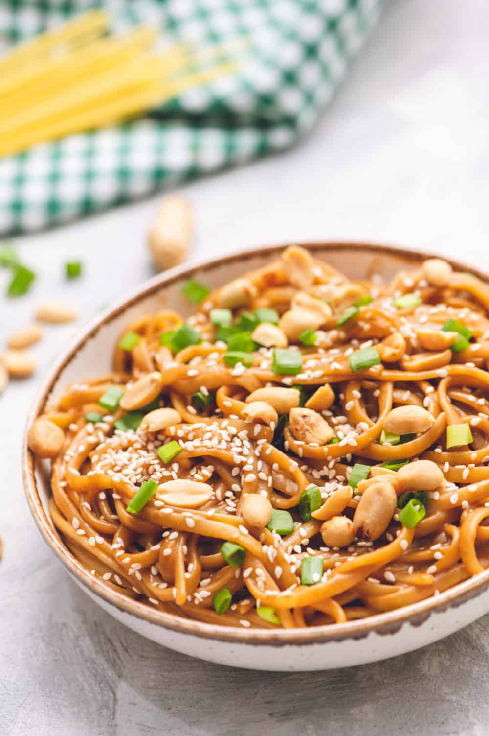 Thai peanut sesame noodles in a bowl with scallops and sesame seeds as garnish.
