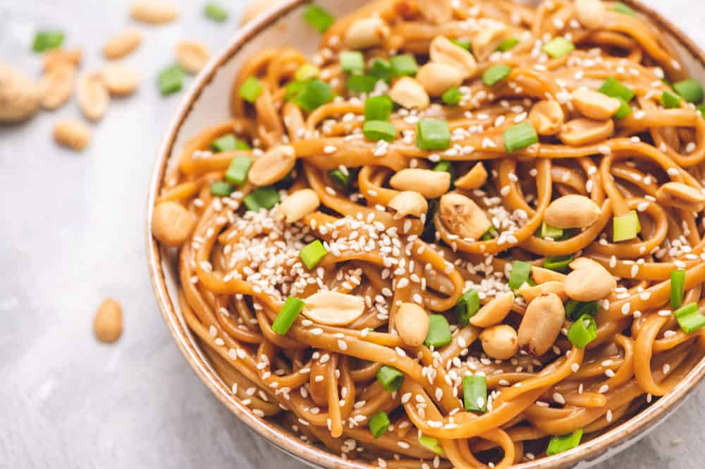 Thai peanut sesame noodles in a bowl with peanut halves garnished with scallops and sesame seeds.